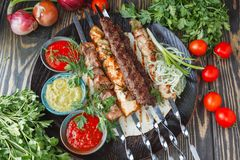 Different meats skewer with vegetables. On wooden tray Stock Image