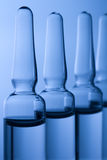 Different medical ampoules on blue background Royalty Free Stock Photo