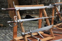 Different medieval styled swords on wooden racks. Many different medieval styled swords on wooden racks Royalty Free Stock Photography