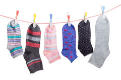 Different men`s and women`s socks on clothes line with clothespi. Several different varicolored men`s and women`s socks hanging on the clothes line with plastic stock photo