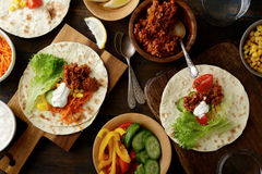 Different mexican Tacos with ground meat, carrots, cucumber, corn, pepper, tomato and lettuce on old wooden table Stock Photo