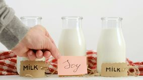 Different milk types soy cow healthy vegan diet. Different milk types. Soy versus cow milk. Healthy eating and vegan diet. Man hand putting a tag in front of a stock footage