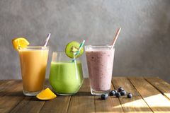 Different milkshakes in glasses. On table stock images