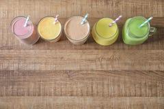 Different milkshakes in glassware on background royalty free stock photos