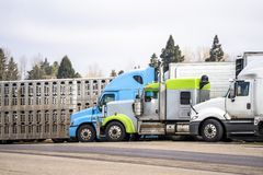 Different model of big rigs semi trucks with different semi trailer stand on truck stop parking place stock photos