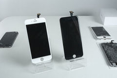 Different modern mobile phones with broken screen on white table royalty free stock photography