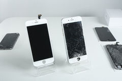 Different modern mobile phones with broken screen on white table.  stock photos