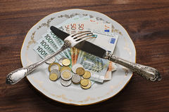 Different money on the plate. US dollars, euros, russian rubles and a big choice of dofferent coins on the vintage plate royalty free stock photography