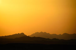 Different mountains and orange sky Royalty Free Stock Image