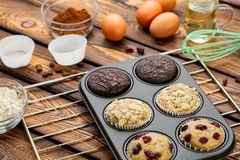 Different Muffins in bakeware or muffin pan on broun wooden background. Basic muffin recipe. Homemade muffins for breakfast or des. Sert. Ingredients stock photo