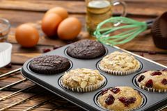 Different Muffins in bakeware or muffin pan on broun wooden background. Basic muffin recipe. Homemade muffins for breakfast or des. Sert. Ingredients stock photography