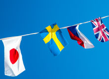 different national flags hanging on a rope on a blue sky background Stock Photos