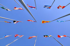 Different national flags and sky background. Different countries national flags on pole together, shown as worldwide, country, and international communication or Royalty Free Stock Images