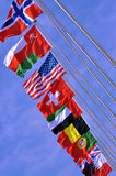 Different national flags under sky. Different national flags on pole, under blue sky, shown as world, country, and international communication or activities Stock Image