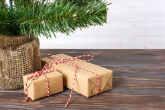 Different New Year`s gifts wrapped in wrapping paper under the Christmas tree branch.  Royalty Free Stock Image