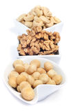 Different nuts. Some bowls with nuts, as macadamia nuts, walnuts and cashews on a white background royalty free stock photo