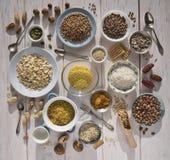 Different nuts, cereals, raisins on plates on a wooden table. Cedar, cashew, hazelnut, walnuts, almonds, pumpkin seeds, sunflower stock photography