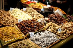 Different nuts and dry fruits in basket for sale at market. Display with Tasty walnut, pecan at the Boqueria market in stock photo
