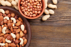 Different nuts in plates Stock Photos