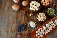 Different nuts and seeds. In wooden spoons and bowls stock images