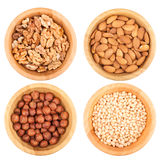 Different nuts in wooden bowls. Isolated on white background, top view Stock Image