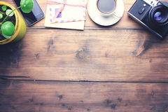 Different objects on table. Coffee, letter, camera, phone and plant on wooden table Stock Photos