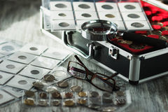 Different old coins, glasses and magnifying glass, Soft focus background Royalty Free Stock Photography