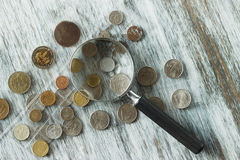 Different old coins and magnifying glass, Soft focus background Royalty Free Stock Photo