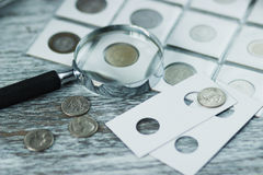Different old coins and magnifying glass, Soft focus background Stock Image