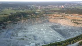 Different old mining machines in large grey quarry aerial