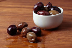 Different olives in white bowl on wooden board Stock Images