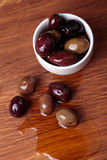 Different olives in white bowl on wooden board Stock Photography