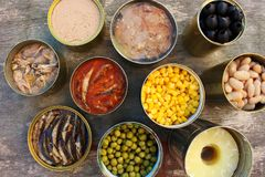 Different open canned food on old wooden background. Top view. Flat lay stock photo