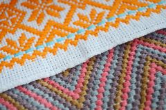 Different orange, pink and blue patterns of embroidery on white fabric. Different orange, pink and blue patterns of embroidery on a white fabric stock photo