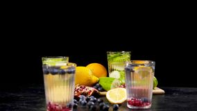 Different organic fruits next to four glasses of detox water. Two made from cucumbers and other two from blueberries, oranges, lemons and pomegranates stock footage