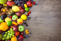 Different Organic Fruits  with  water drops on wooden table back Royalty Free Stock Images