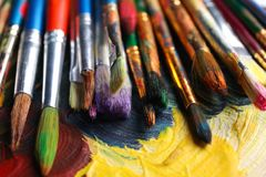 Different paint brushes on color palette. Closeup royalty free stock image