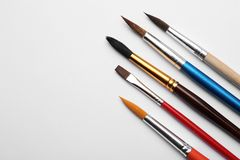Different paint brushes on white background, top view. stock photo