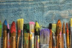 Different paint brushes on wooden background, top view royalty free stock photography