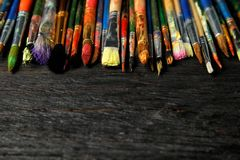 Different paint brushes on wooden table, closeup. stock photos