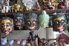 Different painted wooden masks in gift shop, Bali royalty free stock photos