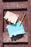 Different paper for ads and pencil. On an old wooden door with shadows from sunlight royalty free stock photography