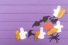 The different paper silhouettes cut out with scissors with autumn leaves made of halloween corner frame. On a purple wooden table. Halloween celebration. Copy Stock Photos