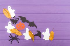 The different paper silhouettes cut out with scissors with autumn leaves made of halloween corner frame. On a purple wooden table. Halloween celebration. Copy Royalty Free Stock Photos