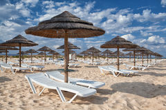 Different parasols and sun loungers on the empty beach. On Tavira island, Algarve. Portugal royalty free stock images