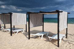 Different parasols and sun loungers on the empty beach. On Tavira island before storm,Algarve. Portugal stock images