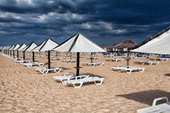 Different parasols and sun loungers on the empty beach on Tavira Stock Photography