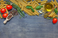Different pasta, condiment, cheese, olive oil and tomatoes on da Stock Photo