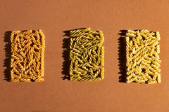 Different pasta in the form of spirals of brown, yellow and green colors on a brown background. Top view royalty free stock photos