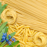 Different pasta lie on the surface. Different pastes on the surface, the background paste, green onions and spring flowers stock images